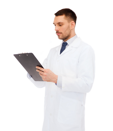 take a note: medicine, profession, and healthcare concept - serious male doctor with clipboard writing prescription over white background