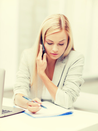 office notes: businesswoman talking on the phone and taking notes