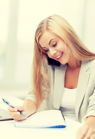 businesswoman talking on the phone and taking notes photo