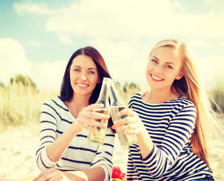 summer, holidays, vacation, happy people concept - smiling girlfriends with bottles of beer or non-alcoholic drinks on the beach photo
