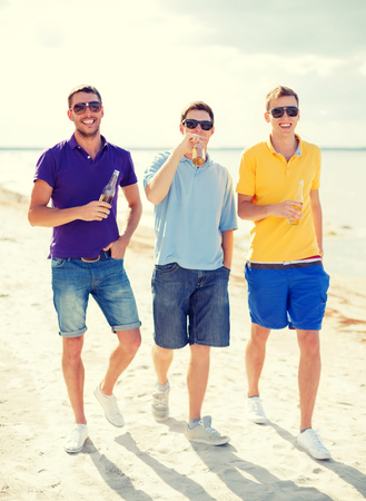 nonalcoholic beer: summer, holidays, vacation and people concept - group of male friends having fun on the beach with bottles of beer or non-alcoholic drinks