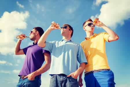 nonalcoholic beer: summer, holidays, vacation, happy people concept - group of male friends having fun on beach with bottles of beer or non-alcoholic drinks Stock Photo