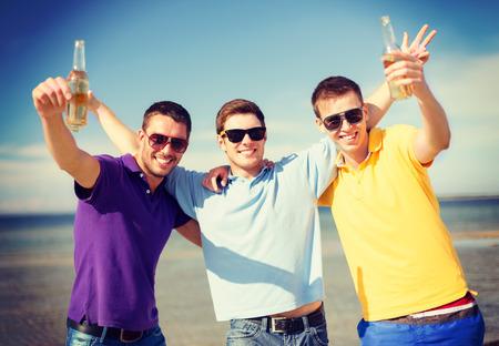 invitando: verano, vacaciones, vacaciones y concepto de la gente - grupo de amigos varones se divierten en la playa con botellas de cerveza o bebidas no alcohólicas