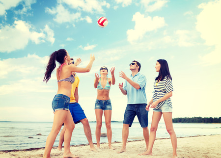 play time: summer, holidays, vacation, happy people concept - group of friends having fun on the beach