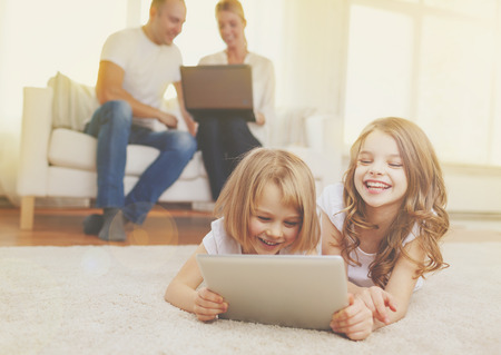 family, children, technology and home concept - smiling sister with tablet pc computer and parents on the back with laptop photo