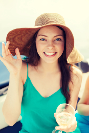 summer holidays, vacation and celebration concept - smiling girl in hat with champagne glass photo