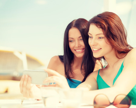 summer holidays, vacation and technology concept - girls looking at smartphone in cafe on the beach photo