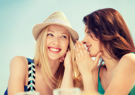 summer holidays and vacation concept - girls gossiping in cafe on the beach