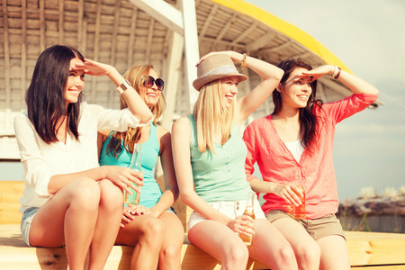 non alcoholic beer: summer holidays and vacation concept - smiling girls with drinks on the beach searching for someone or something Stock Photo