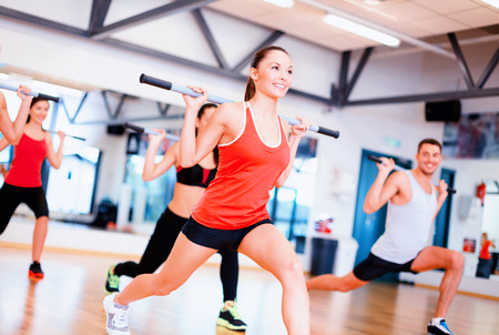 fitness hombres: fitness, deporte, entrenamiento, gimnasio y estilo de vida concepto - grupo de gente sonriente de trabajo con pesas en el gimnasio Foto de archivo