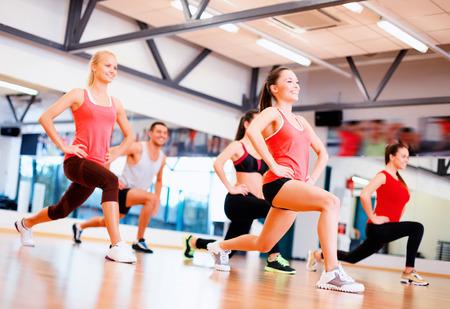 fitness, sport, trénink, posilovna a koncept životního stylu - skupina lidí, usměvavá cvičení v posilovně