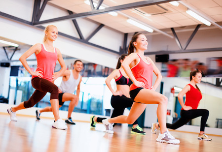 squats: fitness, sport, training, gym and lifestyle concept - group of smiling people exercising in the gym