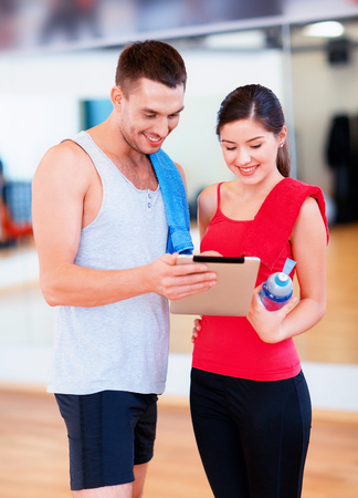 personal computer: fitness, sport, training, technology and lifestyle concept - two smiling people with tablet pc computer and water bottle in the gym