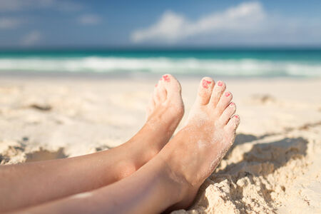 painted toes: summer, beach, leisure and body part concept - closeup of woman legs on sea shore Stock Photo