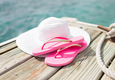 pink shoes: beach, summer, vacations and accessories concept - close up of hat and slippers at seaside Stock Photo