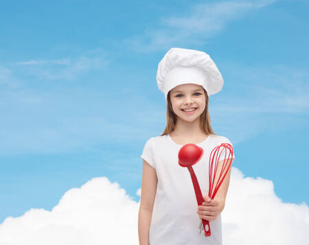 cooking and people concept - smiling little girl in cook hat with ladle and whisk photo