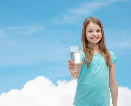 health and beauty concept - smiling little girl giving glass of water Banco de Imagens