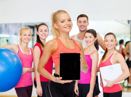 personal computer: fitness, dieting, technology and sport concept - smiling sporty woman showing tablet pc blank black screen Stock Photo