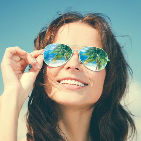 glass reflection: holidays, travel, vacation and happiness concept - beautiful woman in sunglasses with beach reflection