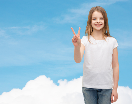 victory sign: gesture and happy people concept - smiling little girl in white blank t-shirt showing peace gesture with fingers