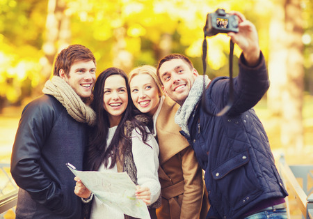 technology, holidays, travel, happy people concept - group of friends or couples having fun with photo camera in autumn park photo
