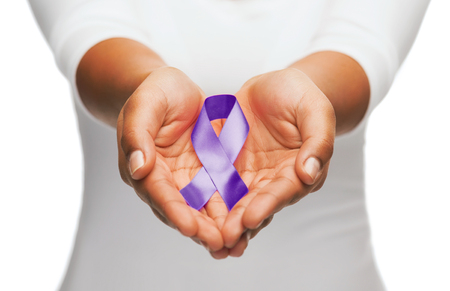 awareness: healthcare and social problem concept - womans hands holding purple domestic violence awareness ribbon