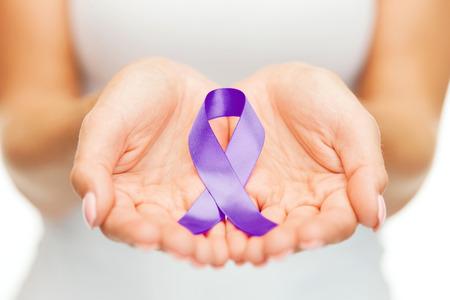 healthcare and social problems concept - womans hands holding purple domestic violence awareness ribbon Foto de archivo