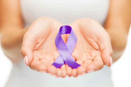 healthcare and social problems concept - womans hands holding purple domestic violence awareness ribbon Stock Photo