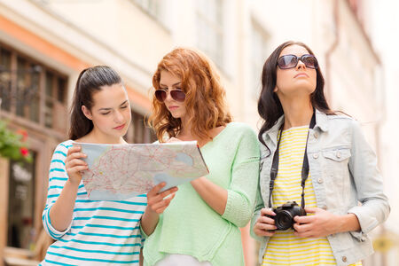 travel guide: tourism, travel, leisure, holidays and friendship concept - teenage girls with map and camera outdoors