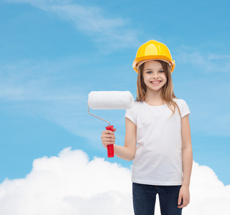 construction and people concept - smiling little girl in protective helmet with paint roller photo