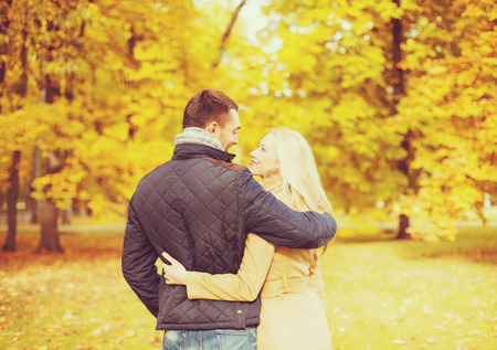 love kissing: holidays, love, travel, relationship and dating concept - romantic couple kissing in the autumn park