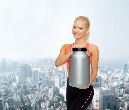 fitness and diet concept - smiling sporty woman with jar of protein photo