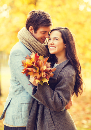 hugging couple: holidays, love, travel, relationship and dating concept - romantic couple kissing in the autumn park