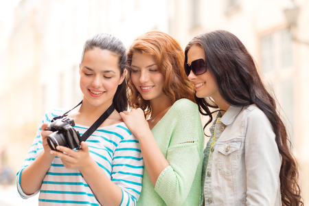 season photos: tourism, travel, leisure, holidays and friendship concept - smiling teenage girls with camera outdoors Stock Photo