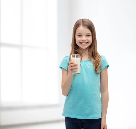 preteen  pure: health and beauty concept - smiling little girl with glass of milk