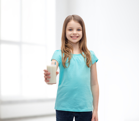 preteen  pure: health and beauty concept - smiling little girl giving glass of milk Stock Photo