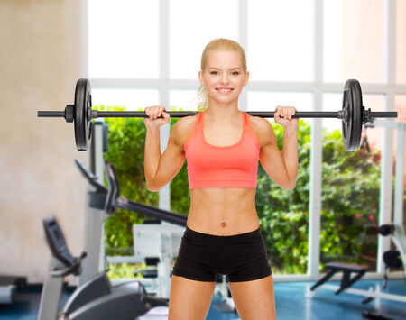 back exercise: fitness, sport and dieting concept - smiling sporty woman exercising with barbell