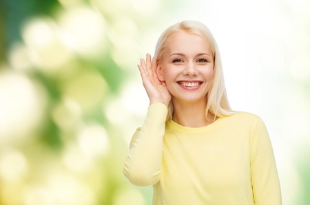 hearsay: gossip, communication and people concept - smiling young woman listening to gossip Stock Photo