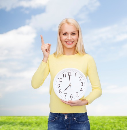 time, education and people concept - smiling young woman with wall clock showing 8 and finger up photo