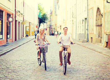 riding bike: summer holidays, bikes, love, relationship and dating concept - couple with bicycles in the city