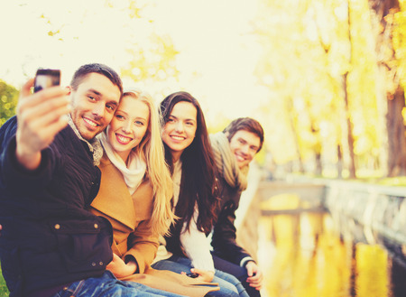 taking photograph: holidays, vacation, travel and tourism concept - group of friends or couples having fun in autumn park and taking selfie