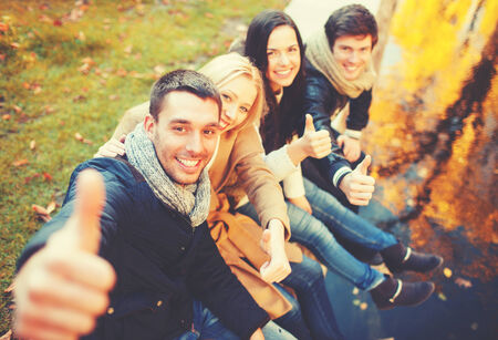 thumbs up group: holidays, vacation, happy people concept - group of friends or couples having fun and showing thumbs up in autumn park
