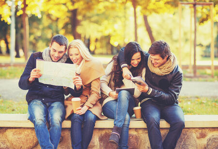 lost city: holidays and tourism, navigation concept - group of friends or couples with tourist map and tablet pc computer in autumn park Stock Photo
