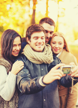 holidays, vacation, travel and tourism concept - group of friends or couples having fun in autumn park and taking selfie photo