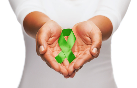 leucemia: cuidado de la salud y la medicina concepto - las manos femeninas que sostienen la cinta de la conciencia del trasplante de órganos verde