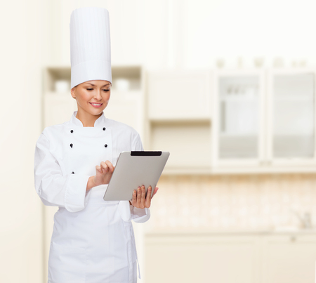 cooking, technology and food concept - smiling female chef with tablet pc computer photo