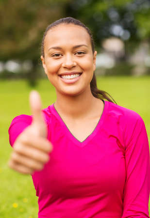 fitness, park, happiness and people concept - portrait of smiling african american woman showing thumbs up outdoors photo