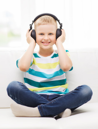 earphone: home, leisure, new technology, childhood and music concept - smiling little boy with headphones at home