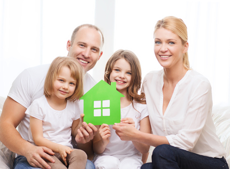 green: real estate, family, children and home concept - smiling parents and two little girls holding green house