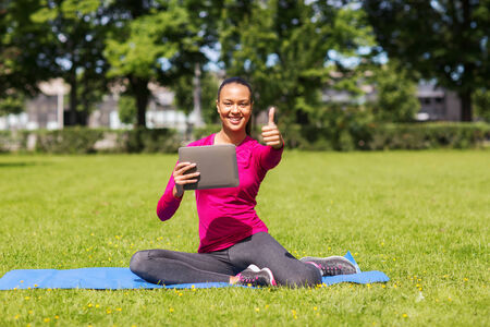 fitness, park, technology, gesture and people concept - smiling african american woman with tablet pc showing thumbs up outdoors photo